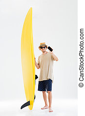 Man in sunglasses holding surfboard and showing blank screen...