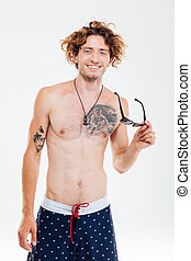 Smiling happy curly man in swim shorts holding sunglasses...