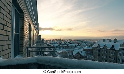 Iced balconies, trees and snowy roofs at sunset 4K shot -...