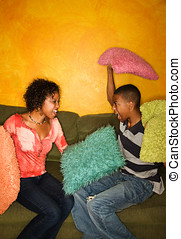 African-Americans having pillow fight - Woman and teenage...