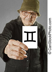 Elderly woman holding card with printed horoscope Gemini...