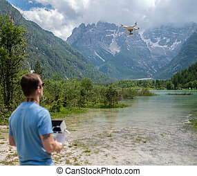 Man controls drone with mountains on background. Alps,...