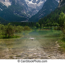 Drone flying over mountain lake. Alps, Italy. - Drone flying...