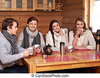 Best friends drinking hot tea in cosy kitchen at winter cottage