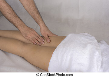 Close up of a woman legs receiving a massage from a man...