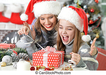 Unwrapping Christmas present - Young beautiful mother helps...