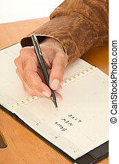 Hand of man writing in day planner about new life - Hand on...