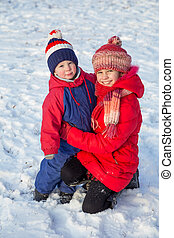 Two happy kids in winter clothes outdoor