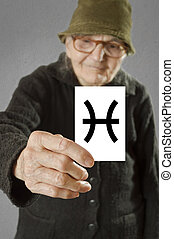 Elderly woman holding card with printed horoscope Pisces...