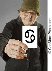 Elderly woman holding card with printed horoscope Cancer...