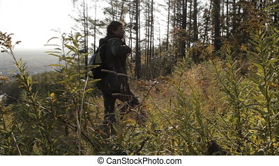 A middle aged man with a beard wearing grey pants, green jacket and yellow boots stopping on a glade, checking his location with a smartphone app and walking on.