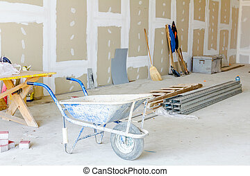 Set of different tools, goods are placed indoor with walls of plasterboard