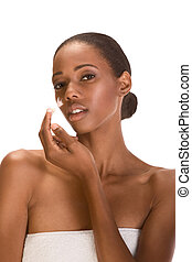 Afro-American girl wrapped in towel putting cream on face