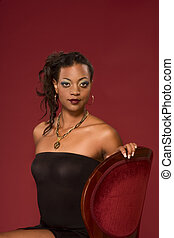 Glamorous portrait of ethnic woman on red chair
