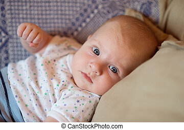 Little baby boy with big blue eyes lying on couch. - Close...