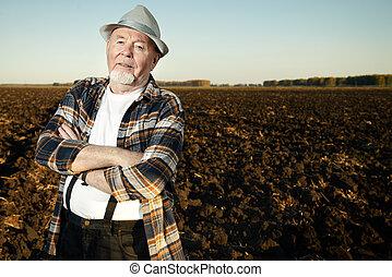 farmer in a plowed field - An elderly farmer standing in a...