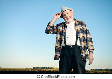 elderly farmer - An elderly farmer standing in a plowed...