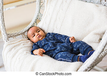 Thoughtful biracial mix of Hispanic and African American infant lying