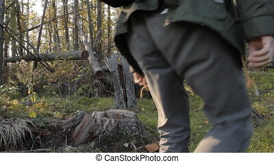 A middle aged man with a beard wearing grey pants, green jacket and yellow boots going uphill, stopping and sitting on a tree stub to have rest. Against an autumnal forest.