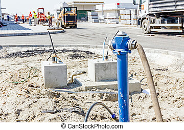 Fire hydrant with blue pipe at building site - Water hose is...