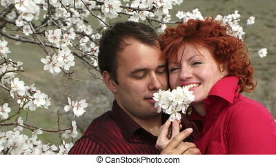 Love couple sniffing flowers