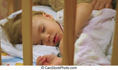 the sweet baby sleeps in a cot with a teddy bear. - the baby...