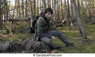 A middle aged man with a beard wearing grey pants, green jacket and yellow boots lit by the setting sun is having rest on a tree stub, wiping his face with a hand and looking aside to look around.