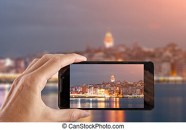 Travel concept. Hand making photo of city with smartphone...