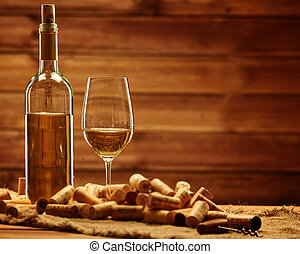 Bottle and glass of white wine on a wooden table among...