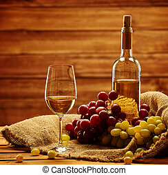 Bottle of white wine, glass and grape on a sack in wooden...