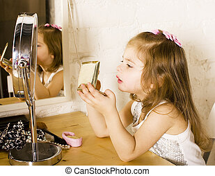 little cute girl with lipstick at mirror, trying do makeup...