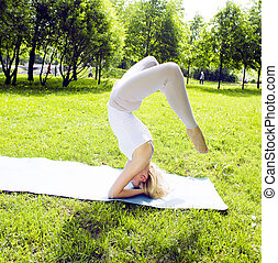 blonde real girl doing yoga in green park, gymnastic head...
