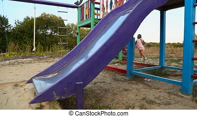 Girl riding on a swing - girl running on the playground to...