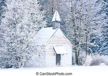 Small woody chapel in frozen snowy forest. Stock photo...