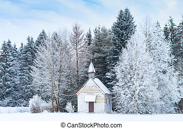 Small wooden chapel on snowbound frosty glade in snowy...