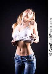 Young sexy woman showing her tummy On black background