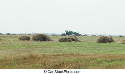 Natural autumn rural background - the grain combine reaps a...