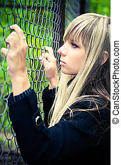 Young woman holding on fence. Soft yellow and blue tinting.