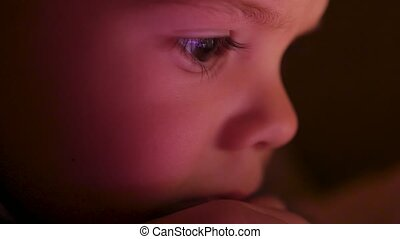 A little boy watches cartoons in the tablet late in the evening closeup face