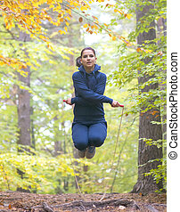 Young beautiful fitness woman skipping rope in forest, autumn colors