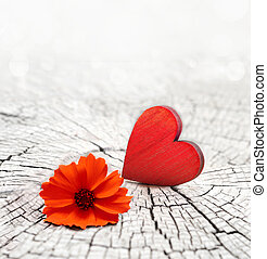red heart on a cracked wooden background and flower - red...