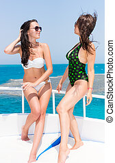 Beautiful women in swimsuit standing on the yacht at a sunny...