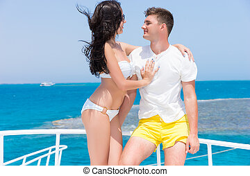 Very attractive young couple standing on the yacht at a...