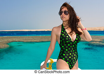 Female in black-green swimsuit standing on the nose of the...