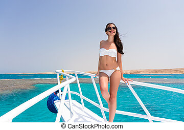 Beautiful female in white swimsuit standing on the nose of...