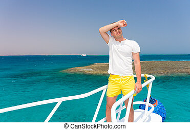 Handsome tired man standing on the yacht at a sunny summer...