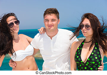 Portrait of young attractive people standing on the yacht at...