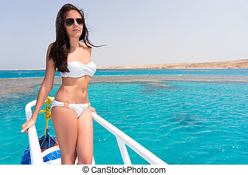 Beautiful girl wearing a white swimsuit and sunglasses on a...