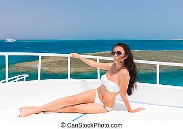 Female in white swimsuit lying on the deck of the yacht at a...