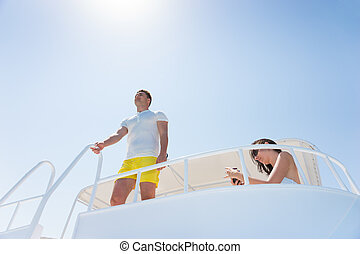 Handsome man standing on the yacht and holding on to railing...